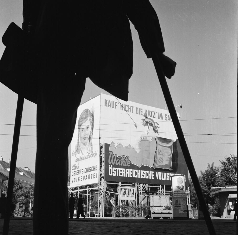 Kriegsversehrter betrachtet ÖVP Wahlplakat 1949.<small>© Okamoto / ÖNB</small>
