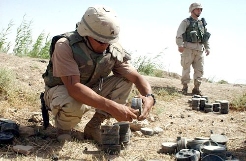 An Army Explosive Ordnance Disposal technician removing the fuze from a Russian-made mine in order to clear a minefield outside of Fallujah, Iraq.<small>© Wikimedia Commons / U.S. Army photo by Spc. Derek Gaines [Public Domain]</small>