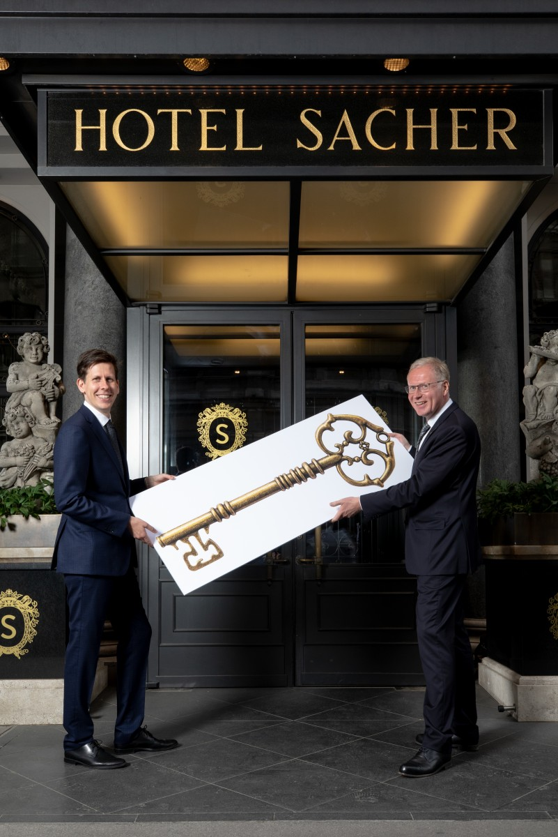 Reiner Heilmann hands over symbolic hotel key to successor Andreas Keese.<small>© Hotel Sacher / Photographer: Jakob Gsoellpointner</small>